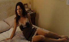 Brunette Rhona Mitra in scenes from one of her movies in bed